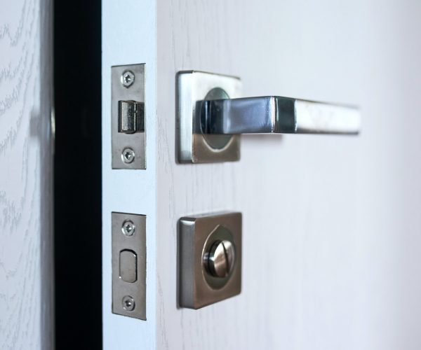 Close-up of a room door with a handle and a metal lock