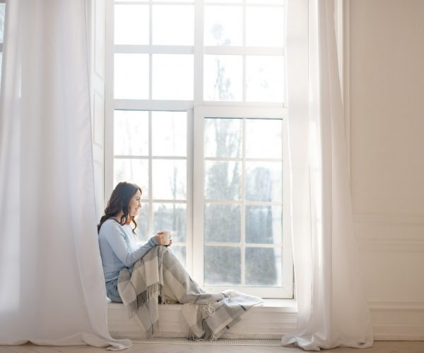 Dark-haired young woman looking out the window